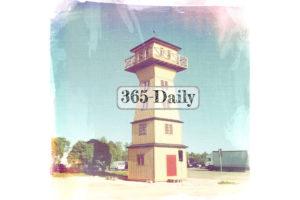Ein quadratischer, hölzerner Turm, dahinter LKW und Autos, geparkt. Der Schriftzug 365-Daily liegt mittig über dem Bild.