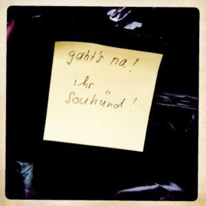 Fundzettel mit der Aufschrift 'Gaht's na? Ihr Sauhünd' auf schwarzem Untergrund
