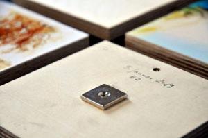 Perspektivische Ansicht von Kunstwerken auf Holz. Im Vordergrund eines mit der Rückseite nach oben, auf dem ein quadratischer Magnet festgeschraubt ist.