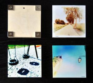 Vier Kunstwerke auf Holz, quadratisch. Eines ist umgedreht. Auf dem Rücken sieht man vier quadratische Magnete an den Ecken verschraubt.