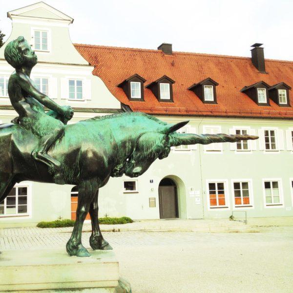 Knabenhafte Figur reitet auf einem kupferoxidgrünen Einhorn, das das Horn nach vorne reckt.