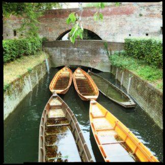 Fünf längliche Boote liegen fast flächendeckend auf einen kleinen Fluss vor zwei kurz hintereinander folgenden, wuchtigen Steinbrücken.