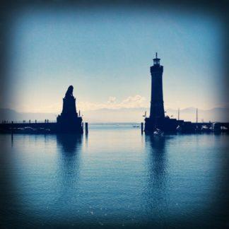 Auf dem bläulichen Bild sieht man die Durchfahrt aus dem Hafen von Lindau in den Bodensee. Links auf der Kaimauer eine Löwenfigur, auf der rechten Kaimauer ein Leuchtfeuer.