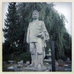 Lebensgroße Stalin-Skulptur auf Sockel vor Nadel- und Laubbaum. Schwarz-weiß-Bild.