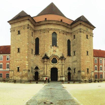 Zentraler Haupteingang und Portal eines Klosters. Quadratisches Bild und wuchtiger Turm.