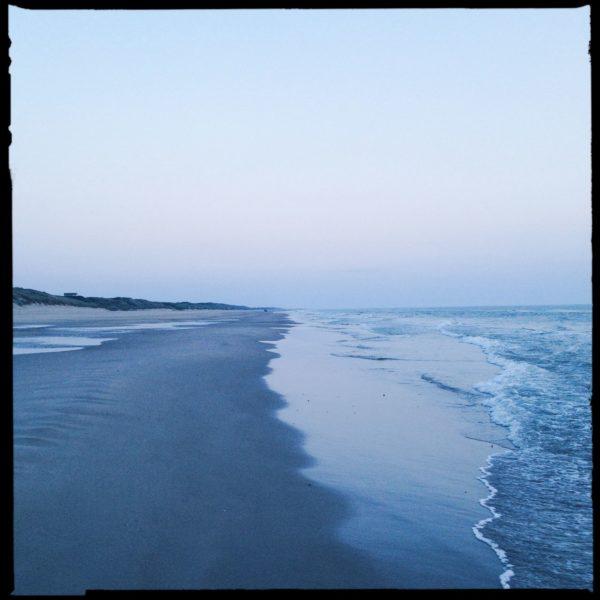 Auf der Linie der ankommenden seichten Wellen stehend blickt man am Strand entlang. Grau-blauer Farbton und blasser HImmel