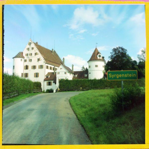 Blick in der Straßenfluch auf ein weißes Schloss. Rechts ein einzelner, runder Turm mit spitzem Dach