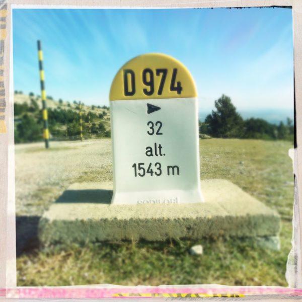 Ein französicher Markierungsstein mit rundem Kopf, Gelb über weiß mit der Aufschrift D 974 und 'alt 1541 m'. Im Hintergrund Straße, verkrüppeltes Gewächs, Schneepflugmarkierungen in gelb-schwarz