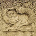 Zwei gemeißelte Fischreliefs, die sich nahezu ineinander schlingen, fast wie ein Yin Yang Symbol