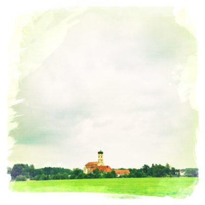 Kirche mit Zweibelturm in weiter ferne, bildmittig. Darüber weiter himmel mit zartgrauer Bewölkung.