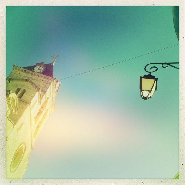Das quadratische Bild zeigt links einen Kirchturm mit Uhr (viertel nach drei), rechts eine scheinbar frei in der Luft hängende Straßenlaterne und eine Andeutung von Hauswand. Türkisfarbener, unwirklicher Farbton.