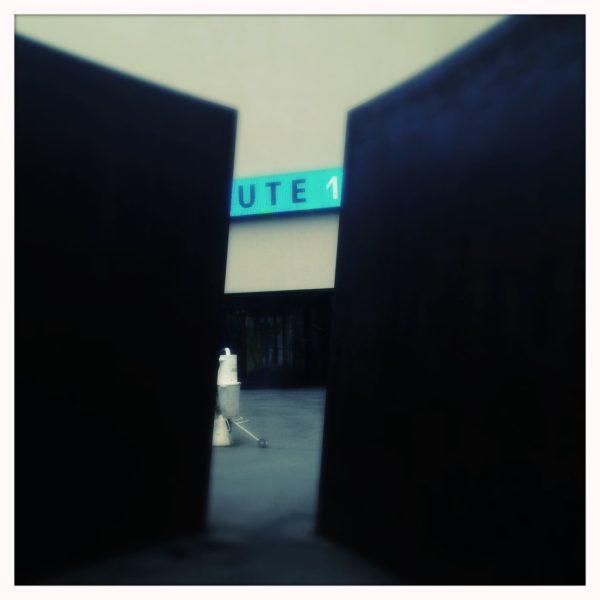 Mitten im Bild ein Ausschnitt aus einer LED-Laufschrift, das das Wort Ute 1 zeigt. die großen Seiten des Bildes sind fast schwarz, zwei senkrechte Stahlplatten, etwa 3 Meter hoch, die nur einen schmalen Streifen freigeben auf die Laufschrift und ein händisch zu bedienendes Arbeitsgerät einer Baustelle.