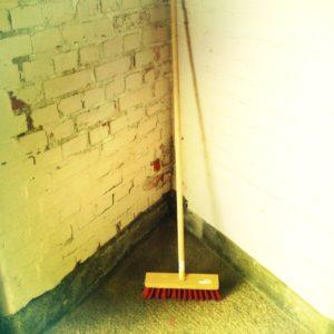 Aufrecht stehender Besen mit roten Borsten in einer Ecke aus weiß getünchten Backsteinen. Auf dem Besen ist noch ein Preisaufkleber zu sehen.