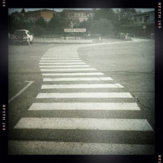 """Ein Zebrastreifenschlängelt sich gewunden über einen großen Parkplatz auf ein Schild zu mit der Aufschrift """"Sapeurs Pompiers"""""""