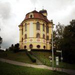 Ein getreppter Weg führt hinauf zur runden Rückseite einer Kirche mit quadratisch abgerundetem Zwiebelturm