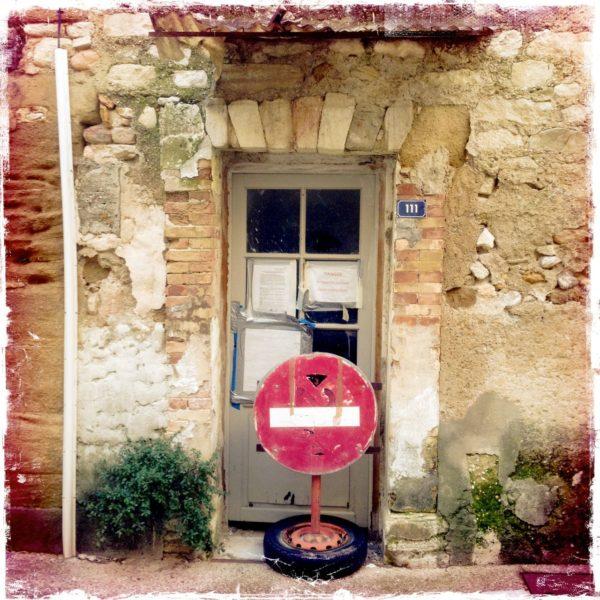 Scheitrecht gemauerte Tür, vor der ein Einfahrt Verboten Schild auf einem alten Autorad, das als Ständer dient steht.