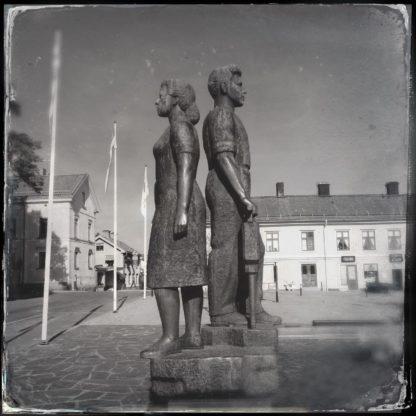 Rücken an Rücken stehen ein lebensgroßer Mann und eine Frau. Schwarz-weiß Bild im Retro-Stil.