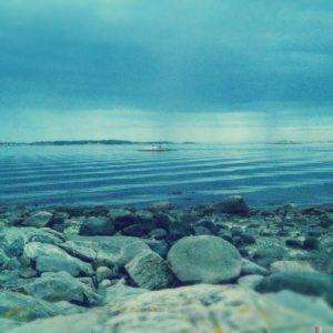 Türkisblaues, sehr körniges, etwas unscharfes Bild, das sanfte Meereswellen hinter steinigem Strand zeigt. In Bildmitte ein schemenhaftes Schiff.