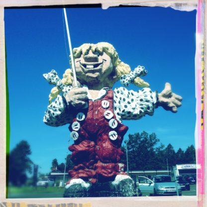 Ein Pipi-Langstrumpf ähnliches Mädchen mit roter Latzhose, Hasenzähnen und Zöpfen, die auch ein bisschen einem Troll ähnelt