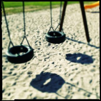 Zwei alte Autoreifen, umfunktioniert zur Kinderschaukel werfen Schatten auf Sand. Rötlich verfärbtes Bild.