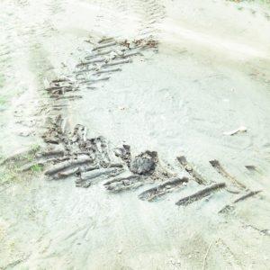 Eine graublaue Spur eines Traktorreifens auf fast weißer Oberfläche.