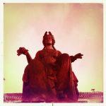 Das rötlich verfärbte Bild zeigt eine sitzende Frau, die einen Lorbeerkranz trägt. Wallendes Gewandt. In der rechten Hand hält sie einen Hängel Trauben.