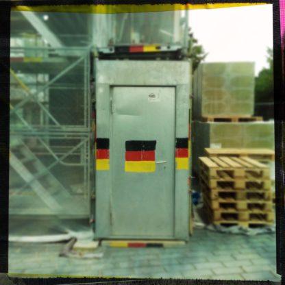 Eine Blechtür mit aufgemalten Deutschland-Farben in einem Bauzaun. Daneben ein Stapel Euro-Paletten.