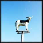 Kalb-Skulptur aus Plastik, bemalt auf einer Stahlkonstruktion. Aus der Froschperspektive gegen den Himmel fotografiert. Merkwürdige Lichtreflexe beflecken das Bild.