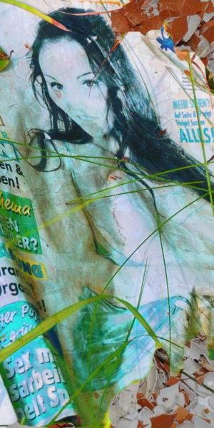 Durch die Ausbleichung durch UV-Licht hat das Motiv einen türkisfarbenen Grundton angenommen. Das zerknitterte Heft, auf dem eine Frau mit langen, schwazen Haaren zu sehen ist, ist verschmutzt mit Erdkrümeln und überwachsen von einzelnen Grashalmen.