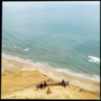 Schräg von links nach rechts zieht sich die Küstenlinie der ruhigen Nordsee vor einem steilen Sanddünenhang. Aus der Vogelperspektive blickt man auf winzige Menschen, die auf einer zerfallenden Mauer ruhen.