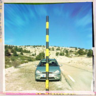 Blick auf einen gelb-schwarzen Pfosten in einer kahlen, steinigen Berglandschaft. Hinter dem Pfosten steht ein Auto, man blickt zentral auf die Motorhaube.