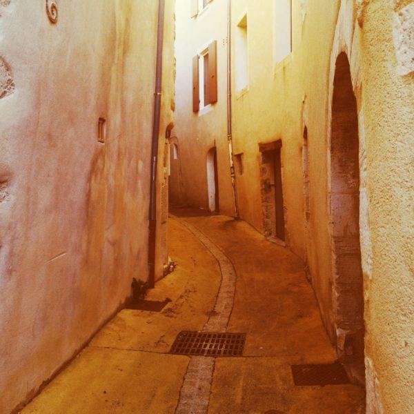 Enge Gasse krümmt sich nach links durch Fassaden voller unregelmäßig verteilter Fenster und Türen. Das Bild hat einen gelblich-beigen Farbton.