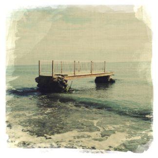Im seichten Wasser an einem Meeresstrand sind die Überreste eines Fußgängerstegs zu erkennen, ein etwa vier Meter langes Etwas.