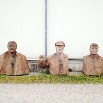 Drei Büsten aus beigebraunen Steinen nebeneinander vor einer Huaswand. Die mittlere Büste reckt die Faust zur Internationalen