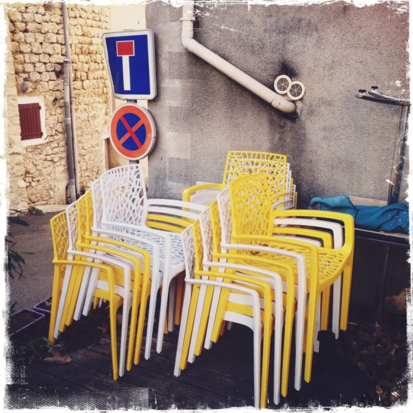Gelbe und weiße Plastikstühle stapeln sich vor einem Sackgassen-Schild in einer verwinkelten französischen Ortschaft