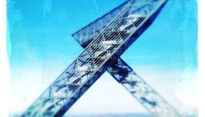 Zwei vergitterte, schräge Aufgänge führen gegenläufig zu einer Aussichtsbrücke. Das Bild hat am Rand viel unschärfe. Es ist cyan-blau bis weiß.