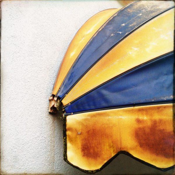 Blau-gelbe kugelförmige Markise füllt mehr als die Hälfte des Bilds. Hauswand fast weiß.