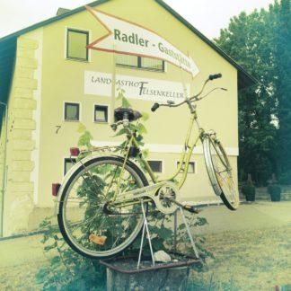 Ein Dreigang-Damenrad aufgebockt auf einem Sockel vor einem Haus mit großem Schriftzug Radlergaststätte