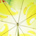 Blick von unten in einen gelben Schirm mit Früchtemotiv und Blattwerk.