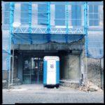 Ein Toi Toi Mietklo vor einer Baustelle. Das Portal wirkt wie eine Bühne. Rechts und links ist das Baugerüst mit Netzen abgehängt.