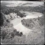 S-förmig schlängelt sich ein Fluss durch einen steilen Abhang. Schwarz-weiß-Bild-