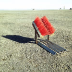 Zwei rote Besensbürsten im 90 Grad-Winkel montiert auf einem Wellblechhalter werfen einen langen Schatten nach links.