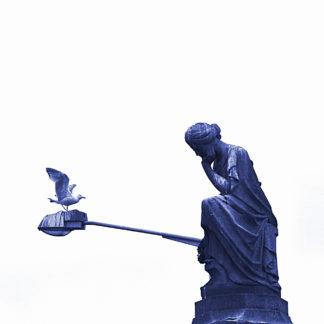 Eine in Denkerpose hockende Frauenstatue vor einem auskragenden Laternenmast, auf dem sich gerade eine Möwe niederlässt. Das Bild hat einen Blauschimmer vor weißem Hintergrund