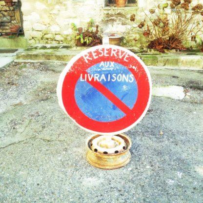 Parkverbotsschild mit französischer Aufschrift improvisiert auf einer Autofelge festgeschweißt.