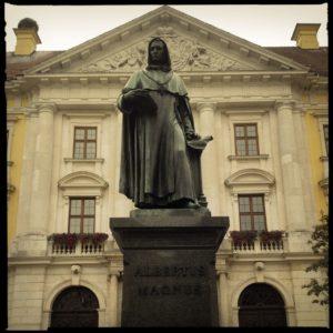 Grau bis grünliche Bronzestatue auf steinernem Sockel vor barockem Gebäude.