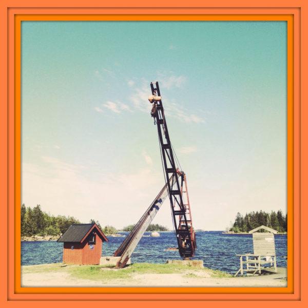 An einem Hafen in den Ostsee-Schären. Ein Kran ragt hoch in den blauen Himmel. Dashinter Meer, Wald, eine kleine Hütte. Das Bild hat einen auffälligen orangenen dreifachen Rahmen.