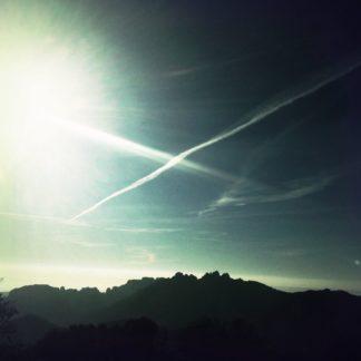 Die oberen Dreiviertel des Bildes zeigen blaugrauen Himmel mit sich kreuzenden Kondensstreifen. Im Unteren Viertel die Silhouette der gezackten Gebirgskette Les Dentelles in der nördlichen Provence.