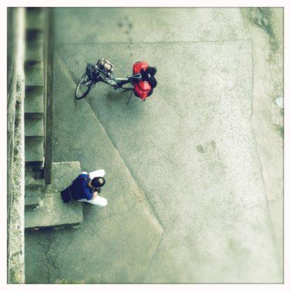 Von oben blickt man auf ein bepacktes Reiserad und einen daneben sitzenden Mann mit Tonsur-ähnlicher Glatze.