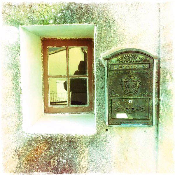 Neben einem winzigen Fenster mit Kreuz-Verglasung hängt ein Briefkasten mit der Aufschrift Lettres. Das Bild hat einen schrillen, grünlich gelben Farbstich.