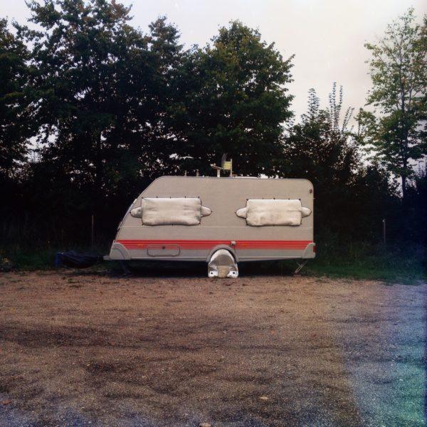 Ein Wohnwagen im Profil vor einer dunklen Hecke. Fenster und Rad sind verhängt, was ihm ein Gesicht gibt.